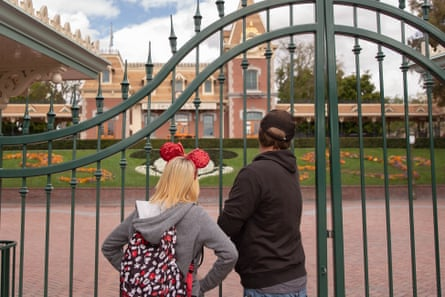 Tourists look through the fence after Disneyland was closed due to the coronavirus.