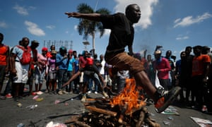 A man jumps over a fire during a voudou ceremony to grant protection to the people, as protesters called for the resignation of President Jovenel Moïse.