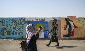 A Sudanese protester and a military school student walk past a mural during a sit-in at army HQ in Khartoum