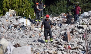 Emergency workers search the rubble of a building that was destroyed in earthquake in Amatrice