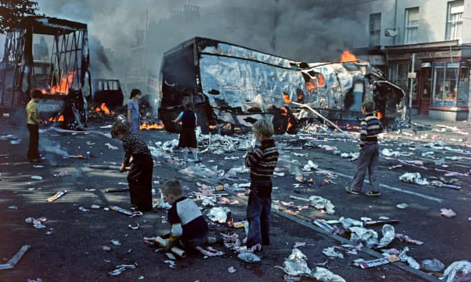 Children playing among debris after riots in west Belfast in 1976.