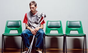 Young man with crutches sitting on hospital chairs