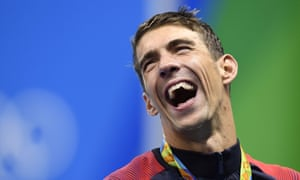 TOPSHOT - USA's Michael Phelps laughs while posing with his gold medal on the podium of the Men's 4x100m Freestyle Relay Final during the swimming event at the Rio 2016 Olympic Games at the Olympic Aquatics Stadium in Rio de Janeiro on August 7, 2016. / AFP PHOTO / GABRIEL BOUYSGABRIEL BOUYS/AFP/Getty Images
