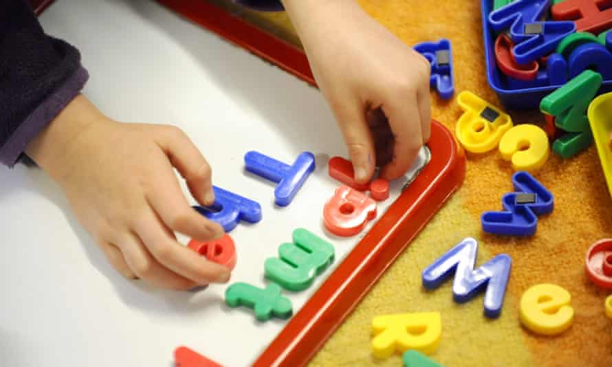 An early years child playing with magnetic alphabet
