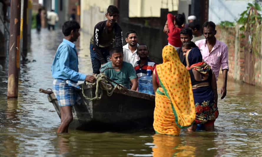 Residents wade through floodwater near the banks of the Ganges in Allahabad, India.