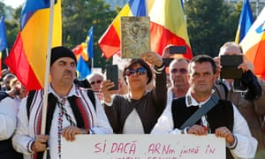 Romanians holding national flags attend a protest against new measures ordered by the government during the fourth wave of the pandemic in Bucharest.