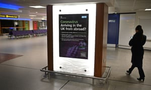 A UK government advert giving information about coronavirus at Manchester airport.