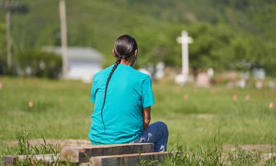 Een man zit en bidt in een veld waar de stoffelijke resten van meer dan 750 kinderen zijn begraven op de plaats van de voormalige Marywell Indian Residential School in Coventry First Nation in Saskatchewan, vorige maand.
