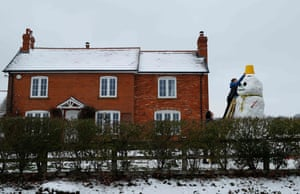 A child adds the finishing touches to a snowman near Hartley Wintney, Hampshire