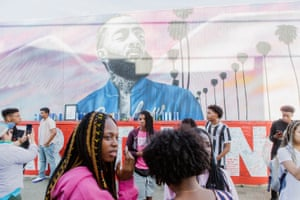 Fans come to take pictures and pay their respects in front of murals of Nipsey Hussle.