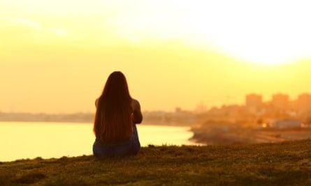 A single woman watching a sunset.