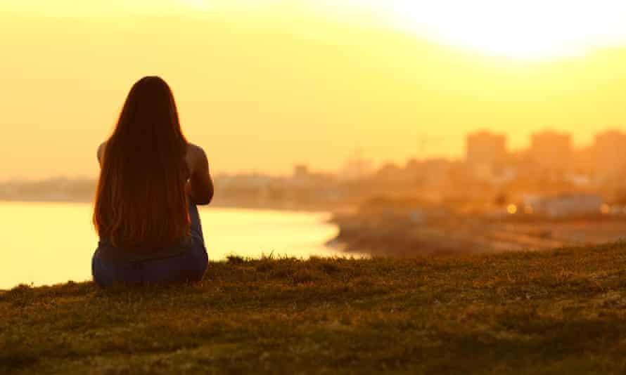 Pensive woman views a city sunset