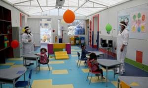 Teachers in protective gear at a Bogota kindergarten on Friday