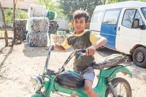 Ercan rides his father's motorbike during a break, in Macedonia, where he collects rubbish to sell.