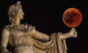 "A ""blood moon"" eclipse beside a statue of the ancient Greek god Apollo in central Athens"