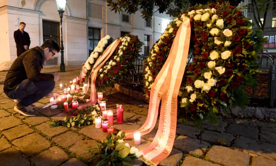 A man lights a candle next to floral tributes at the scene of the attacks in Vienna.