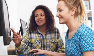 Businesswoman Giving Computer Training to younger woman In Office