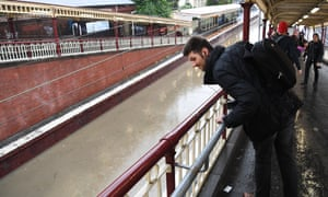A pedestrian looks at flood water at South Yarra train station in Melbourne on Friday. The issued Bureau of Meteorology a severe thunderstorms warning for Victoria on Saturday morning.
