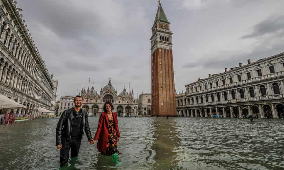 Tourists brave the flood water in St Mark's Square, Venice, in October last year.