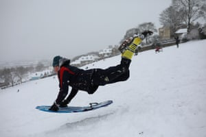 A young man takes a running jump down a snow covered hill with his sledge in Rochester
