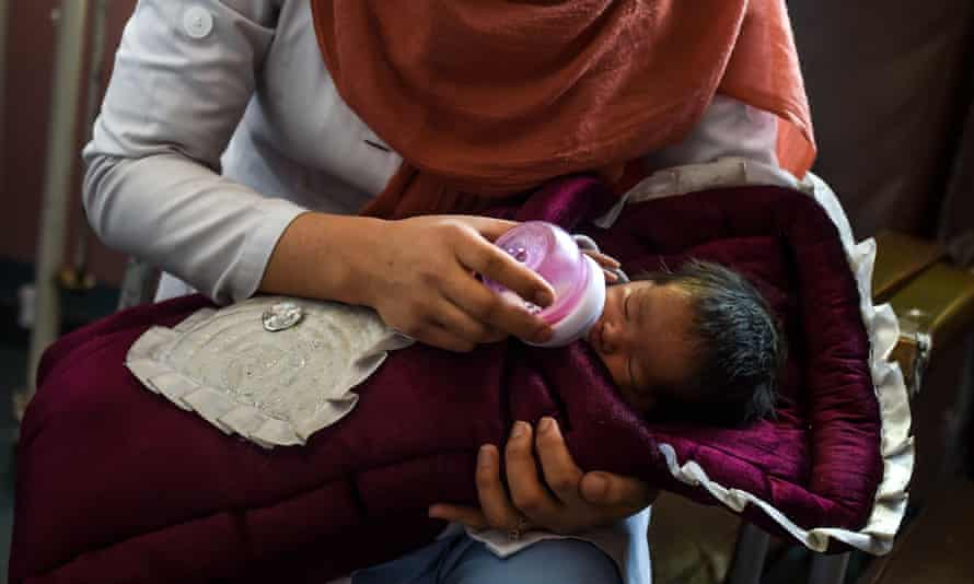 Nurse feeds baby after mother killed by gunmen in attack on maternity hospital in Kabul, Afghanistan