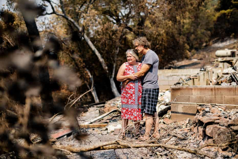 Jim and Leonore Wilson embrace next to the remnants of their house, on 29 August 2020, in Napa.