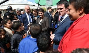 French Prime minister Manuel Valls (2nd R) talks with children next to Education minister Najat Vallaud-Belkacem and Minister of State for Cities, Youth and Sports, Helene Geoffroy. Asked whether headscarves should be banned by law from universities, Valls replied: 'It should be done.'