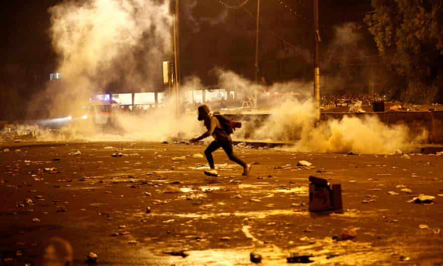 A demonstrator runs from tear gas fired by Iraqi security