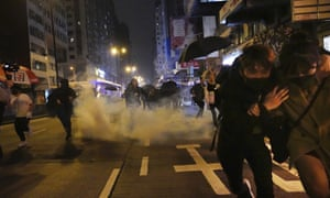 People react as police fire teargas during protests in Hong Kong