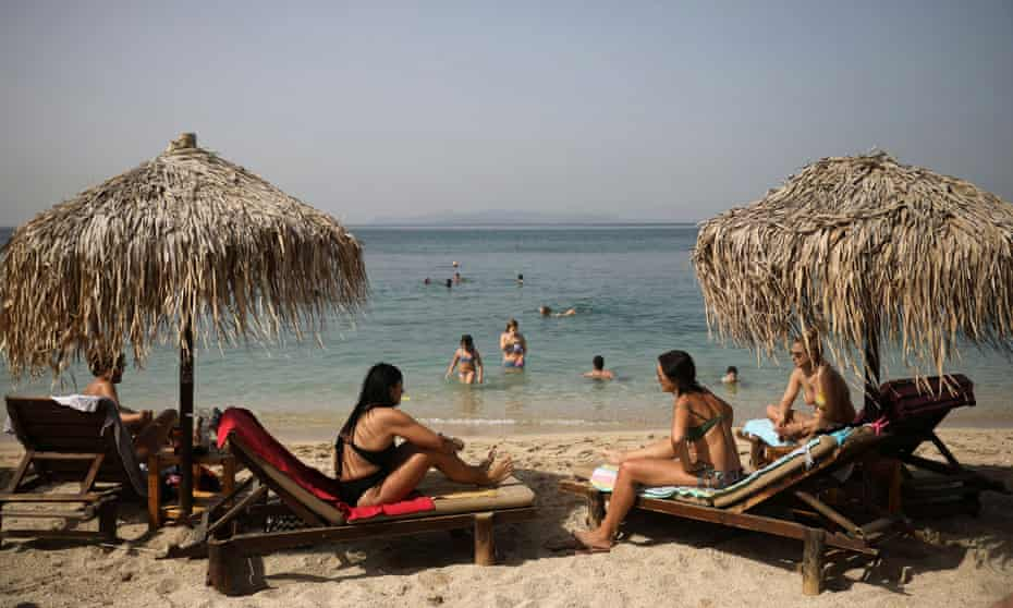 People enjoy the sun in Athens as beaches in Greece are officially reopened to the public following the easing of measures against the spread of coronavirus.
