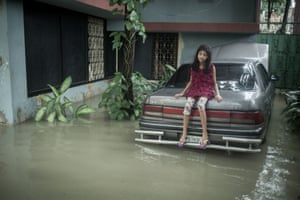 Eight-year-old Saraf sits on a submerged car in Chittagong, Bangladesh