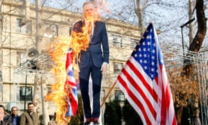 Iranian hardliners burn a cutout poster depicting British ambassador to Iran Robert Macaire along with during a memorial for passengers of Ukraine airplane in Tehran.