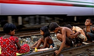 Bangladeshi children play on a railway line while a train passes by at Tejgaon, Dhaka
