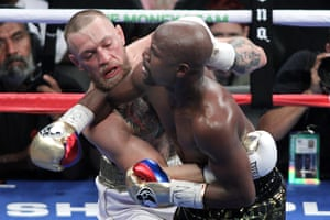 Mixed martial arts star Conor McGregor (L) competes with boxer Floyd Mayweather Jr. during their fight at the T-Mobile Arena in Las Vegas, Nevada on August 26, 2017. Floyd Mayweather outclassed Conor McGregor with a 10th-round stoppage on August 26 to win their money-spinning superfight and clinch his 50th straight victory. / AFP PHOTO / John GurzinskiJOHN GURZINSKI/AFP/Getty Images