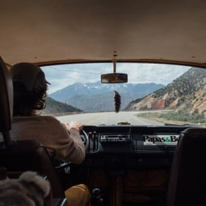 James Barkman at the wheel of his VW van in a photo taken looking out the windshield at the Rockies, Utah, US
