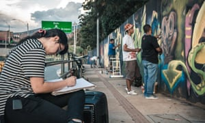 Young people learn about graffiti art on the streets of Medellín.