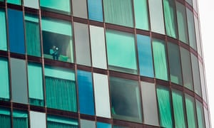 A woman looks out of the window of a Melbourne hotel on Monday where travellers returned from overseas are being held in isolation for a mandatory 14 days as the Australian government tries to contain the spread of coronavirus.