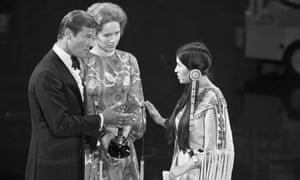 Sacheen Littlefeather refuses Marlon Brando's best actor award, presented by Roger Moore and Liv Ullmann.