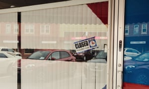 A closed sign is posted in the window of a store in downtown Lexington, Nebraska.