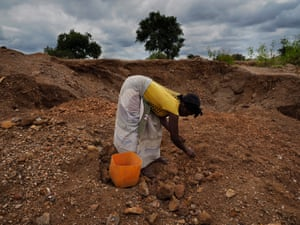 Elsewhere on the contaminated former mine site, women and children crush rock to sell as gravel.