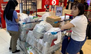 Panic buying: People fill shopping trolleys in Singapore, where the alert level has been raised to orange, its second-highest level