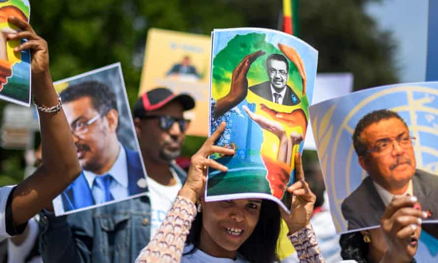 People hold placards of Tedros Adhanom Ghebreyesus, the new WHO director general, during a rally on his campaign trail
