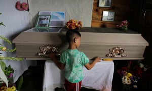 A child touches the coffin of Nelson Espinal, who was shot dead outside his home on 18 December 2018 in Tegucigalpa, Honduras.