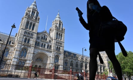 A pedestrian wearing PPE walks past the Natural History Museum, which will reopen on 5 August.