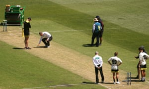 Players and officials inspect the MCG pitch