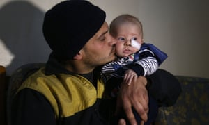 Saeed al-Masri, a member of the Syrian Civil Defence in eastern Ghouta, holds his three-month-old son, Yehya
