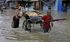 An Indian rickshaw puller makes his way through a flooded street in Calcutta on Sunday 2 August 2015.