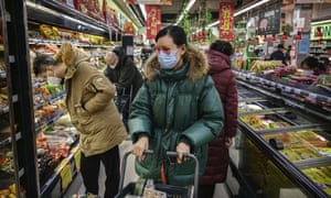 A woman wears a protective mask in a Beijing supermarket. The WHO has declared the coronavirus a global emergency.