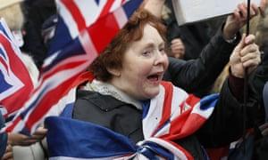 Pro-Brexit demonstrators wave flags outside Parliament.