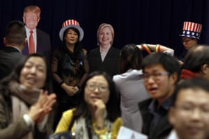 A woman poses with Donald Trump and Hillary Clinton as people watch a live telecast